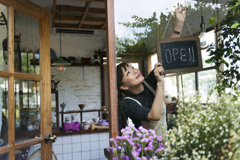 Asian woman hanging open sign in the window of her local business