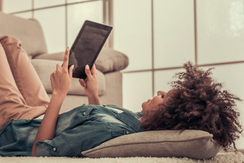 African American woman laying down looking at tablet