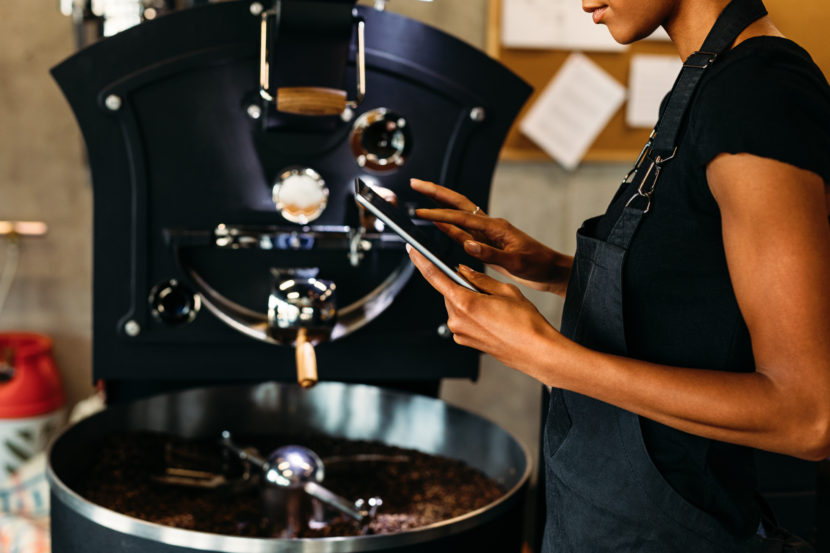African American woman holding tablet at coffee roasting facility