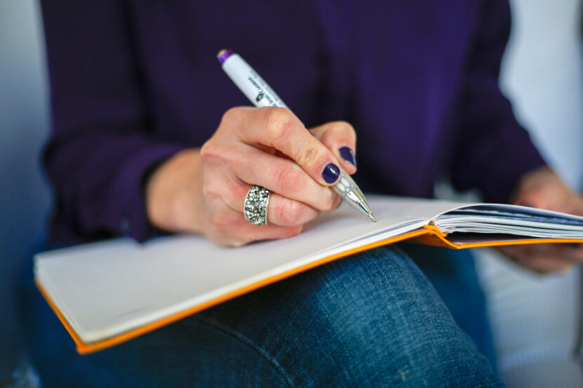 White woman with blue nail polish writing in an orange notebook
