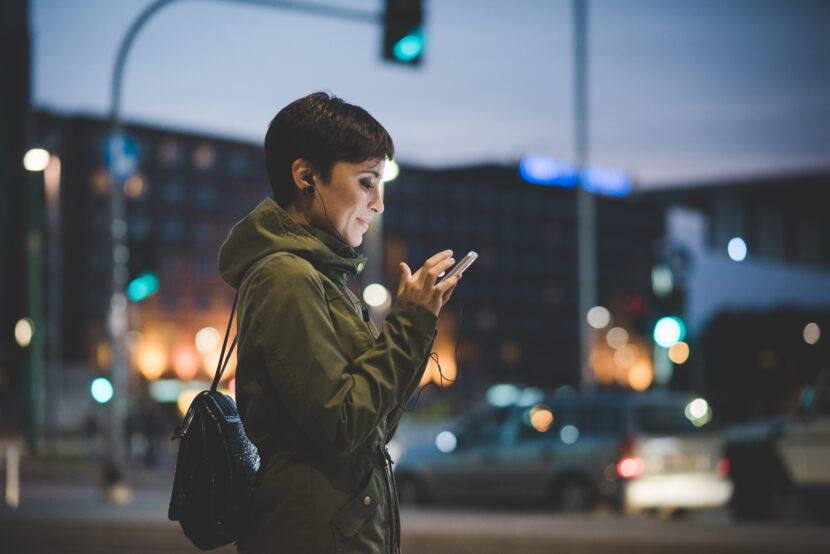 Woman with short brown hair in green coat outside in the evening looking at cell phone